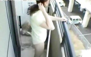 Asian girl masturbates on the balcony of her apartment